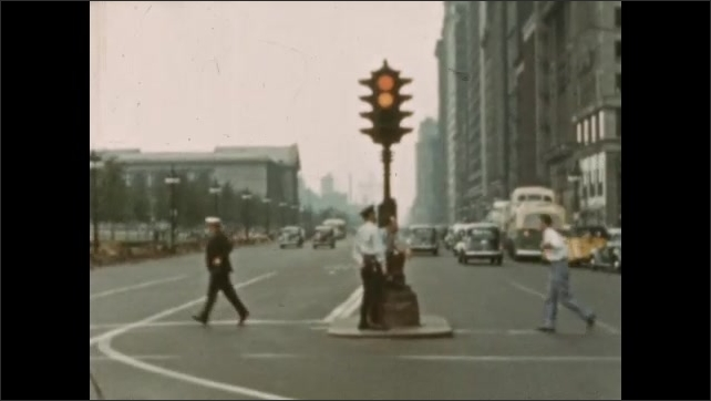 1930s: MEXICO: man walks in city. City buildings. People wait for traffic light to change. Cars in city.