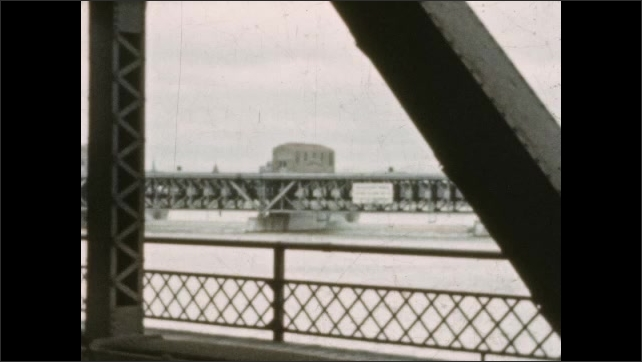 1930s: MEXICO: weir on river. View across water. View from paddle steamer. Car under bridge