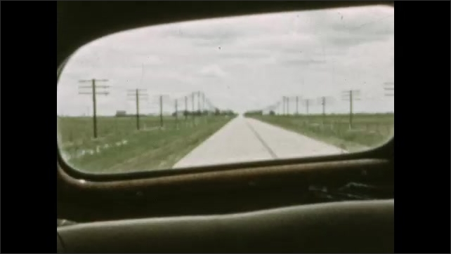 1930s: MEXICO: view of road from car window. Trip through Nebraska. Pylons by road. House in field. Clouds in sky. Hay in field.