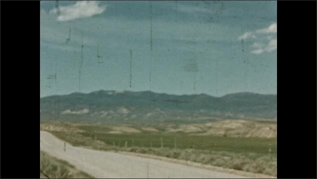 1930s: MEXICO: car drives along road in Colorado. View across plains towards mountains. Clouds over hills