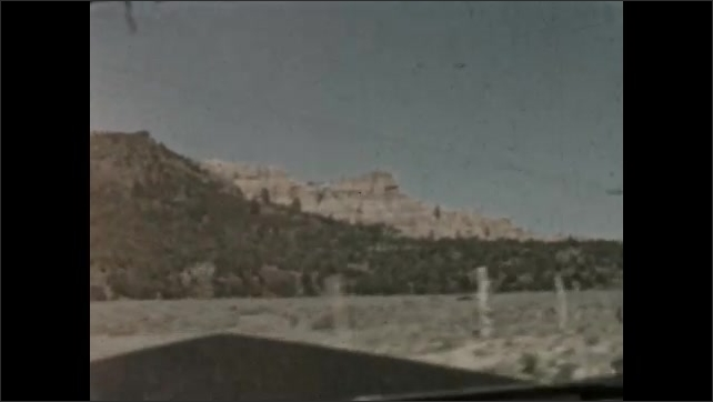 1930s: MEXICO: mountains on horizon. View across landscape from road. Sandstone mountains. Drive beneath arch.