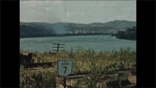 1930s: Sign for Route 7, Ohio next to river. Man bent over opened hood of a car.