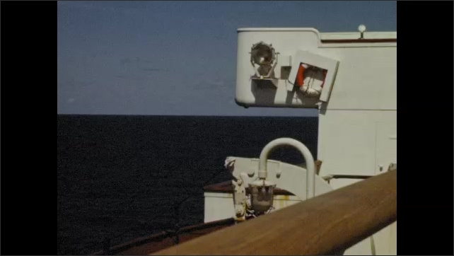 1950s: View of the Atlantic from Queen Elizabeth's cruise ship deck. Man stands at railing and looks out to sea. Wooden lifeboat on the QEII.