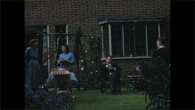 1950s: Family stands in an English garden behind a house and serve themselves from a buffet. Man pours orange squash.