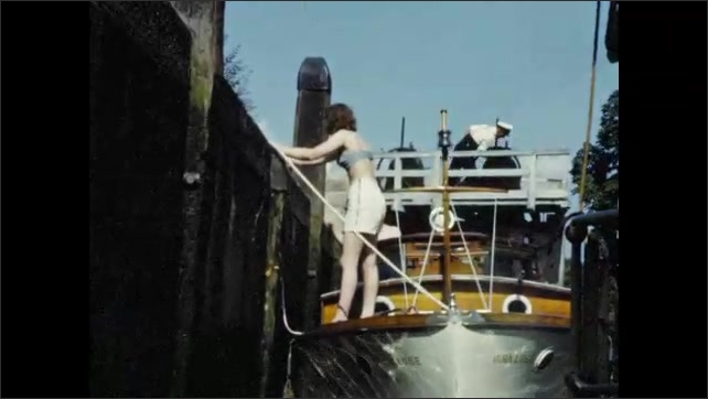 1950s: Boat moves through water.  Swans swim and fight.  Woman stands on boat.  Boat moves through canal lock.