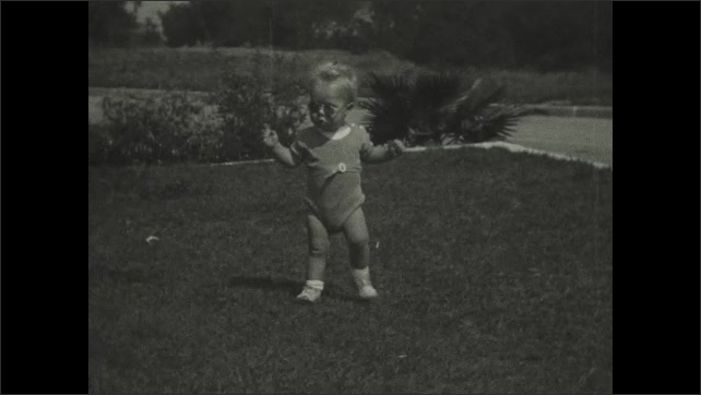 1930s: UNITED STATES: toddler walks across grass. Boy learns to walk. Toddler wears sunglasses.