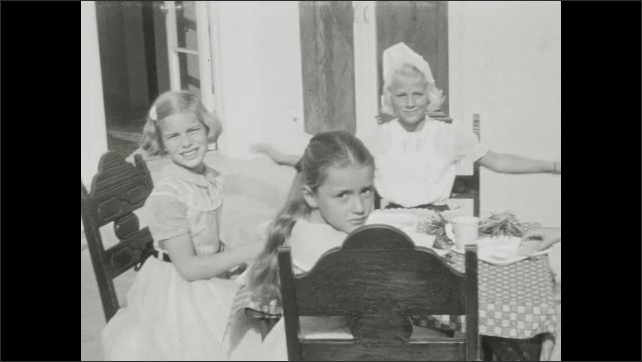 1930s: UNITED STATES: girls sit at table. Girl looks at camera. Girl makes faces for camera. Girl eats party food.