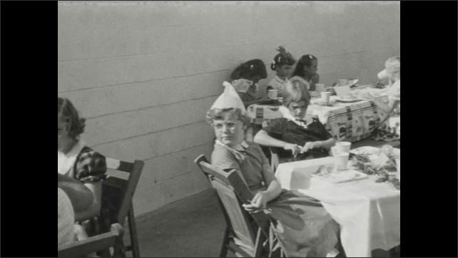 1930s: UNITED STATES: girls sit at table at birthday party. Girl eats food. Lady at party. Girl walks around tables.