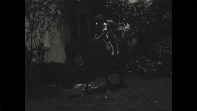 1930s: Three children ride on back of horse around yard.