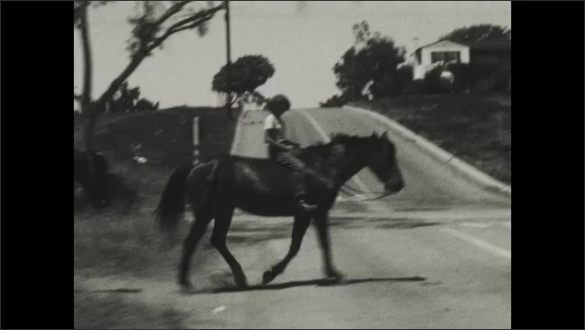 1930s: Two children ride separately on two horses down side of road in neighborhood. They cross a street together.