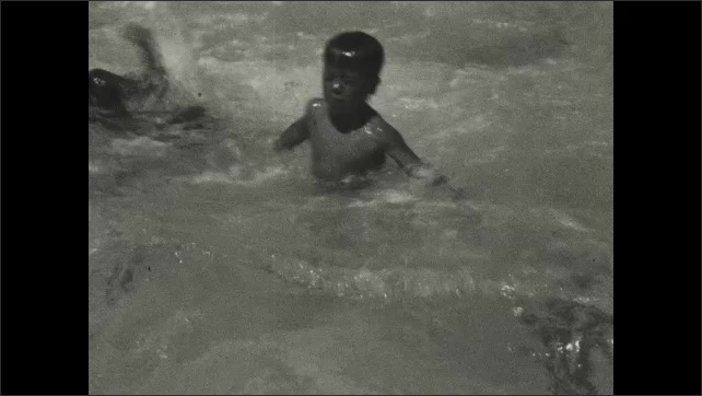 1930s: Three boys lined up on edge of public pool dive in together. Boy walks across shallow area of pool.