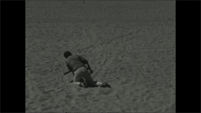 1930s: Man chases chair around sand on his knees. Man grabs chair, wrestles with chair, fights chair.