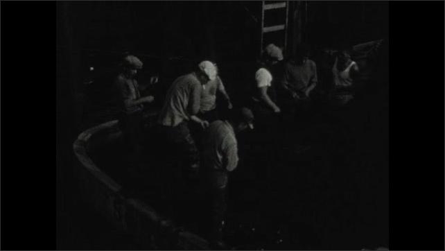 1930s: Men work on deck of ship.