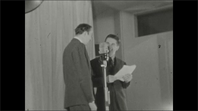 1930s: Studio.  Men stand at microphone together and speak.  Man waves arms.