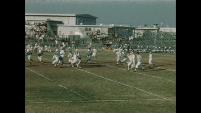 1940s: UNITED STATES: players wait for ball. Man runs with ball. Players chase man with ball