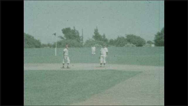 1940s: Boy runs to second base in slow motion and tags up. Boy sprints to third base.
