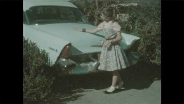 1940s: Teenage girl polishes baby blue car Desoto with fins with a polishing mitt.