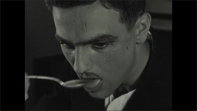 1930s: UNITED STATES: close up of man's face. Man licks lips. Man eats soup at table. Man drinks tea from spoon. Man reads newspaper