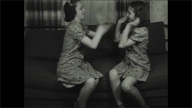 1930s: UNITED STATES: man send children to bed. Girls clap hands on sofa.
