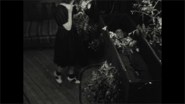 1930s: UNITED STATES: family stand by coffin of child. Girls bring flowers to coffin. Girls cry by coffin. Girl wipes face with handkerchief.