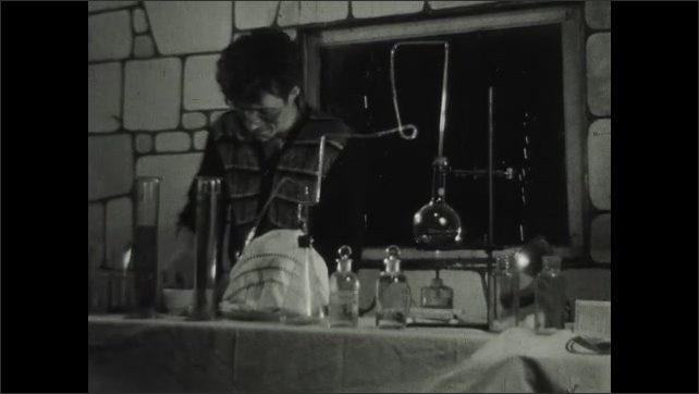 1930s: UNITED STATES: mad scientist in lab. Potions and glass beakers on desk. Man sprinkles dust over object