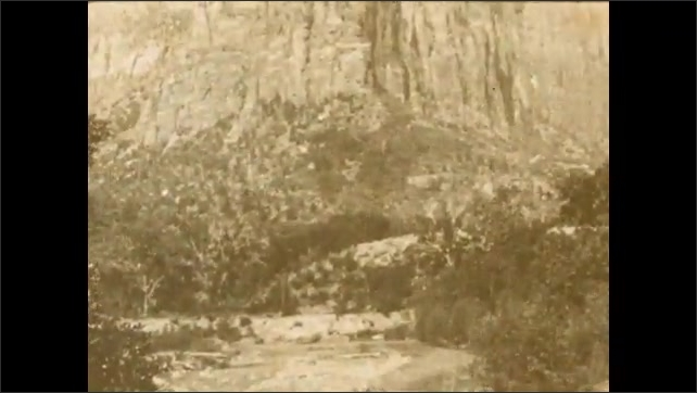 1920s: UNITED STATES: river in valley. Cliff face and mountains