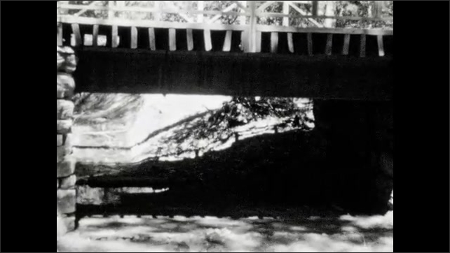 1920s: UNITED STATES: view of mountains from valley. Bridge over river. Buildings in Zion