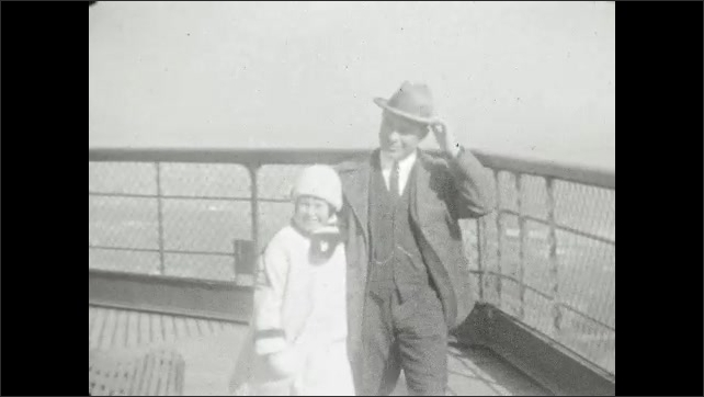 1920s: UNITED STATES: lady and girl on Eiffel Tower. Man and girl on Eiffel Tower. Couple walk around Eiffel Tower. Man holds hat against wind