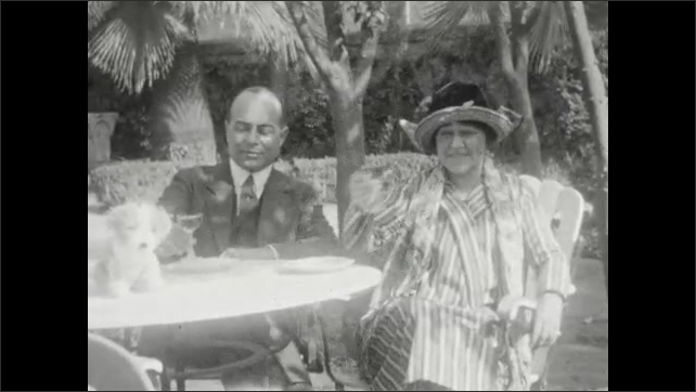 1920s: waiter carrying two glasses of wine, waiter serves wine, man and woman drink wine, young girl looks inside of a large planter