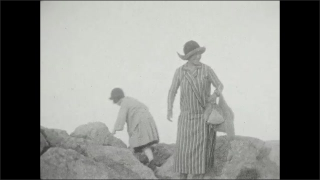 1920s: ancient ruins built on top of a hill, woman and girl climb onto and walk across rocks