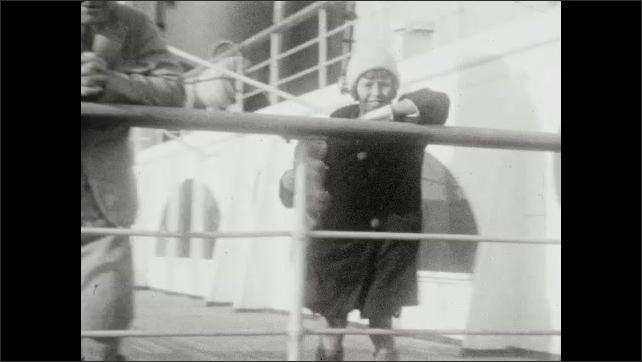 1920s: Pan across deck, smokestacks on ship. Man and girl on ship, pose on railing. Woman and girl walk toward camera. Woman and girl walk away from camera.