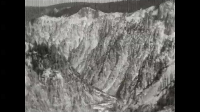 1920s: High angle, tilt up river in canyon. People on platform over waterfall, pan to falls.