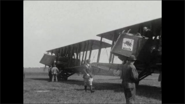 1920s: Man stands by cannon, looks at camera. Mobile gun turret vehicle. Pilot in jodhpurs walks in front of two antique planes. Another angle of planes.