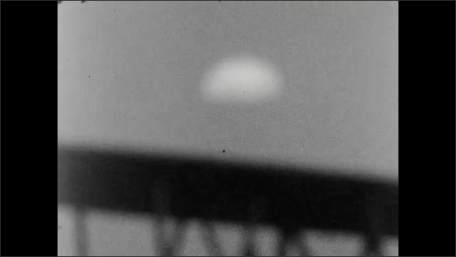 1920s: Out of focus - two men walk, parachute in the sky. In focus - a blimp flies over buildings, a crowd watches from a rooftop.