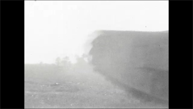 1920s: Tanks, trailers, and other weird looking vehicles drive and speed around a dirty field. One trailer tows a cannon. Most do not have standard wheels, but tank treads