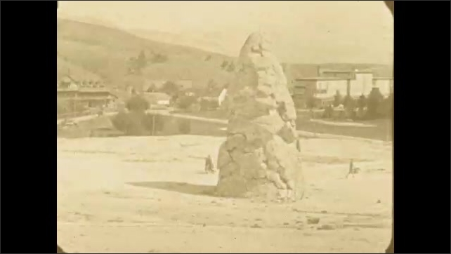 1920s: A huge mound or rock formation in the middle of an empty field surrounded by buildings. Tiny people walk behind the mound.