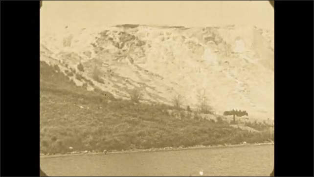 1920s: Two cars drive up a hill with a lake in the foreground and a snowy mountain in the background. A small group of men and women hike up the hill behind the first car.