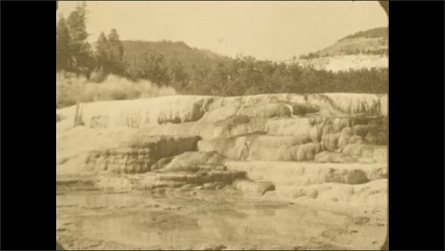 1920s: Static shot of a rock formation in the foreground with trees and mountains in the background.