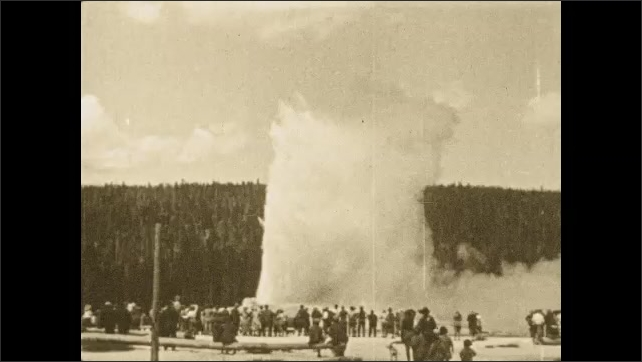 1920s: Crowd of people watch geyser Old Faithful erupt in Yellow Stone National Park. Title card.