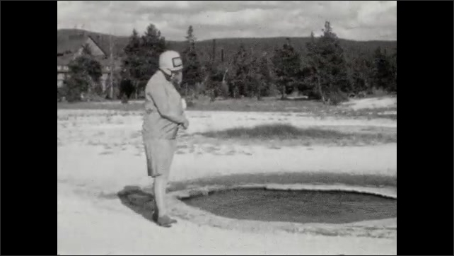 1920s: Exterior of Old Faithful Inn. Title card. Woman stands on edge of pond, bends down and dips finger in pond. Woman runs down small hill. Woman walks up small hill and looks over ledge.