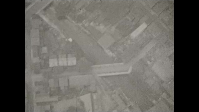 1920s: Shot through the window of a blimp in the sky. Several urban neighborhoods and buildings. A train goes down the tracks, also from above.