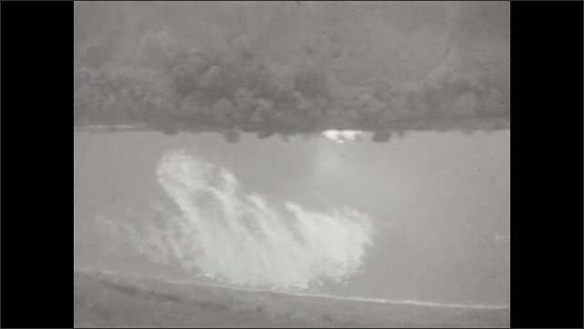 1920s: Shot through the window of a blimp in the sky. A winding river leading back to a dam and beyond. A road with tiny cars on the edge of the river. Contraptions on the underside of the blimp.
