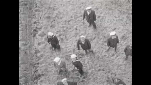 1920s: Shot from inside blimp: groups of sailors in white caps pull ropes to help dock blimp. From ground level: sailors pull blimp along ground. Three little girls giggle and smile on front porch.