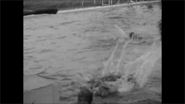 1920s: Three girls back stroke across swimming pool. Spectators watch. Girls dive into the pool, swim, splash, climb out and dive again.