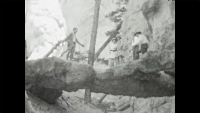 1920s: People pose on rock bridge. Man sits on rock bridge, jumps off.