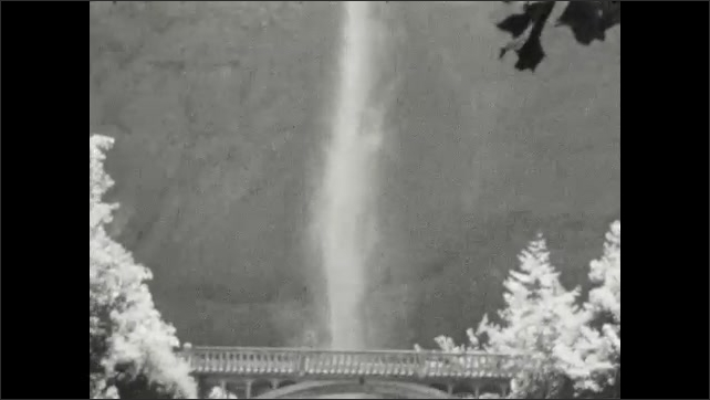 1920s: Water falls down mountain, passes bridge. Person stands at railing, watches waterfall.