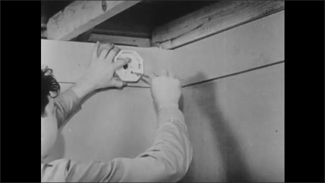 1940s: UNITED STATES: man places junction box above entrance in hallway. Man screws junction box to wall with screwdriver.