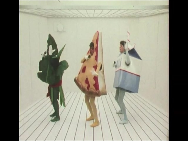 1980s: Woman dressed as pizza sings into mic. Man dressed as carton of milk sings into mic. Woman dressed as green leaf sings into mic. Costumed people sing and dance.  Costumed performers bow.