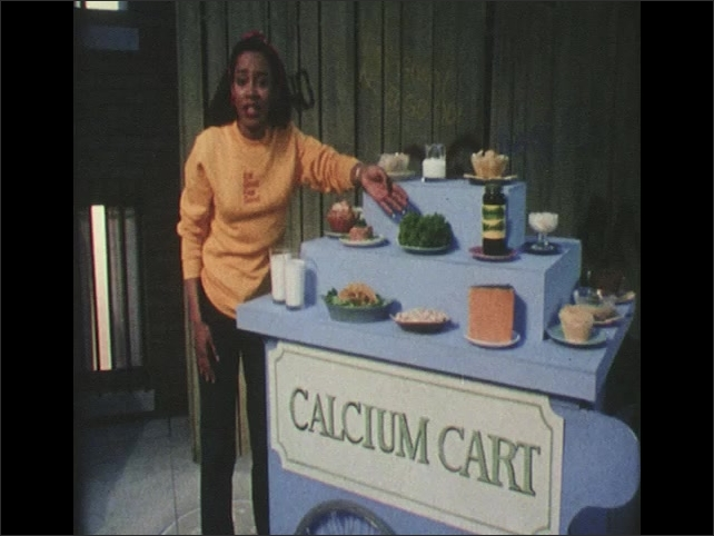 1980s: Woman claps. Woman speaks and points to foods on display cart. Woman lifts glass of milk from cart. Woman lifts up plate of tacos.