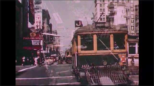 UNITED STATES 1950s: A shot of a busy crossroads in a city.  The front of a trolley car.